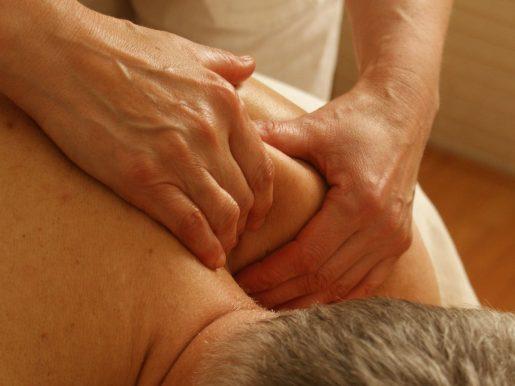 A therapist massages a patient's shoulder.