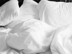 White pillows and blankets unmade on a bed.