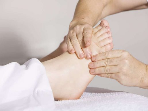 A therapist massages a patient's foot in an effort to ease pain.